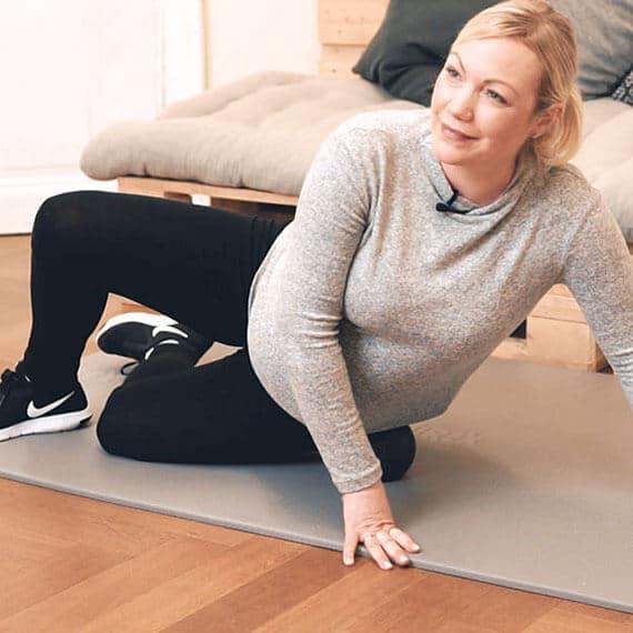 Schwangere Frau macht eine Hüftübung mit einer Faszienrolle