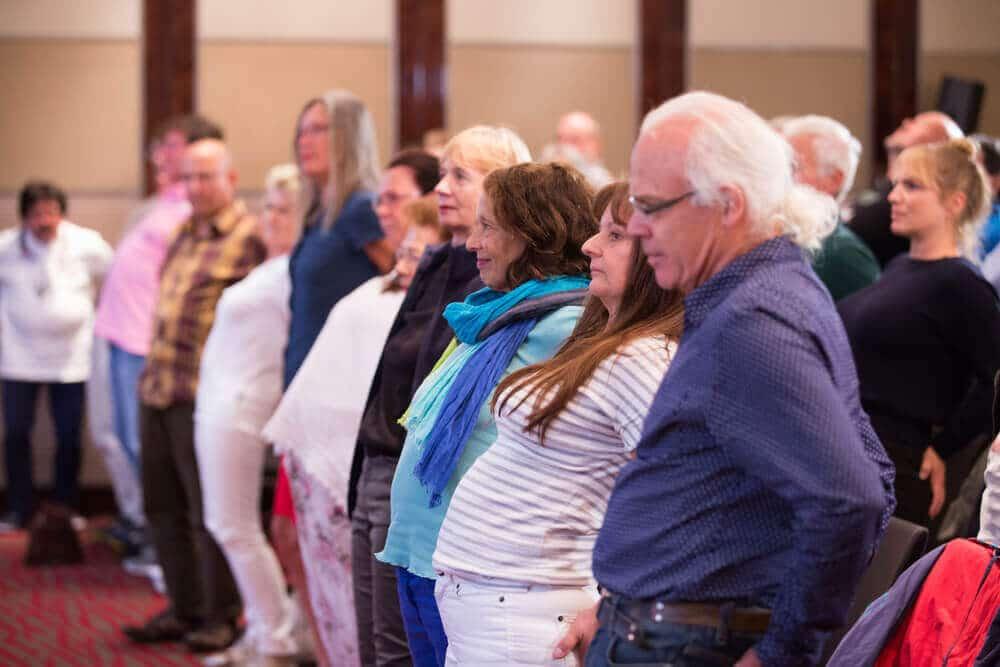 Zuschauer während eines Vortrages machen gemeinsam eine Übung nach