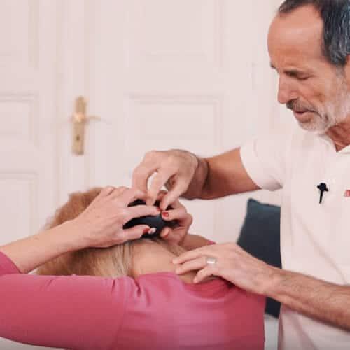 Frau rollt zur Entspannung der Nackenmuskeln mit der Mini-Rolle