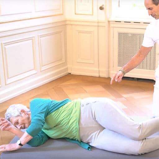 Ältere Dame liegt seitlich auf einer Matte, Roland Liebscher-Bracht zeigt auf ihren Rücken und erklärt dabei etwas.