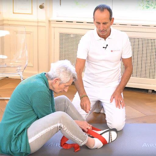 Ältere Damen zieht im Sitzen an Übungsschlaufe, welche um ihre Füße liegt. Die Beine sind leicht aufgestellt und angewinkelt, die Fußsohlen berühren sich jeweils. Neben ihr kniet Roland Liebscher-Bracht.