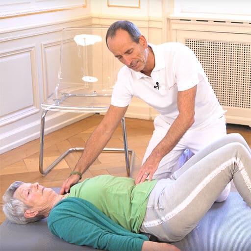 Ältere Dame liegt rücklings auf einer Matte, die Füße aufgestellt. Roland Liebscher-Bracht legt seine Hände auf ihre Schulter und Bauch und erklärt etwas.