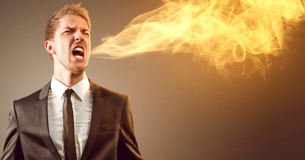 Ein Mann spuckt Feuer als Metapher für sein Leiden unter Sodbrennen