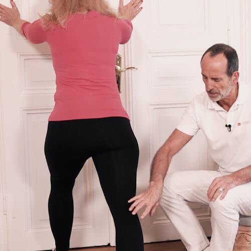 Roland Liebscher-Bracht zeigt einer Frau eine Übung gegen Knieschmerzen