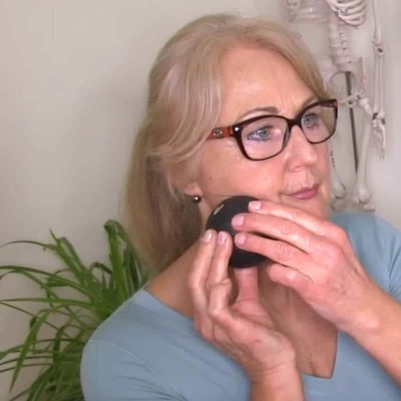 Patientin führt Übung mit Mini-Kugel an Kaumuskulatur aus