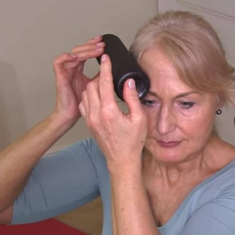 Eine Frau massiert ihre Schläfe mit der Mini-Faszienrolle.