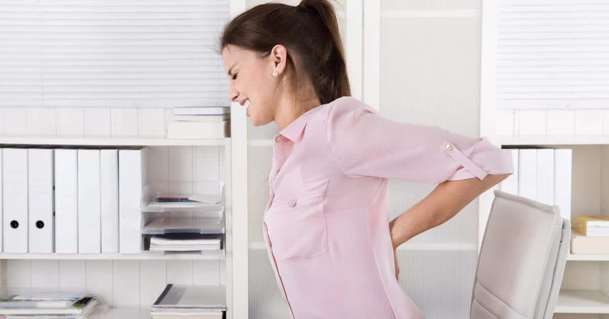 Eine Frau im Büro greift sich mit schmerzverzerrtem Blick an den Rücken.