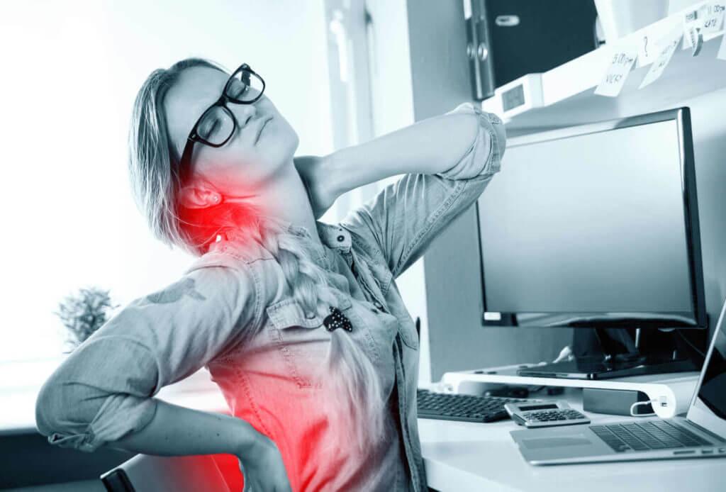 Eine Frau sitzt vor einem Computer und hat Schmerzen im Nacken und im unteren Rücken