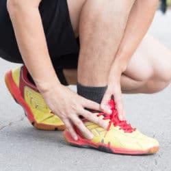 Ein Mann in Sportkleidung greift sich in der Hocke an seinen Fuß.
