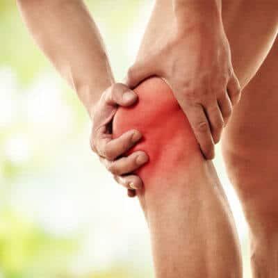 Mann hält sich das Knie vor Schmerzen