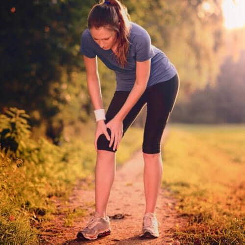 Frau hält sich nach dem Joggen das Knie vor Schmerzen