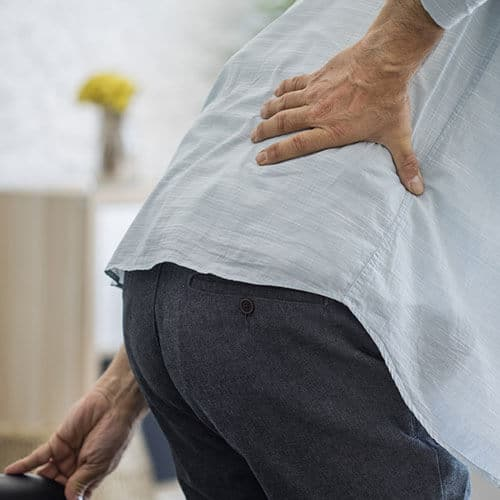 Ein Mann hält sich vor Schmerzen die Lendenwirbelsäule, die als Folge seiner Hypermobilität überlastet ist