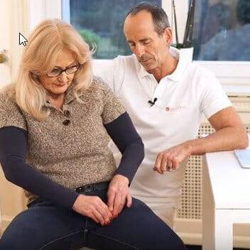 Schmerzspezialist Roland Liebscher-Bracht zeigt einer Patientin eine Übung mit der Minikugel an der Oberschenkel-Innenseite gegen Schmerzen im unteren Rücken