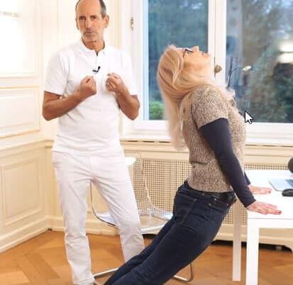 Schmerzspezialist Roland Liebscher Bracht zeigt einer Patientin eine Dehnungsübung gegen Schmerzen im unteren Rücken