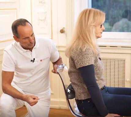 Schmerzspezialist Roland Liebscher-Bracht zeigt einer Patientin eine Übung mit der Medi-Rolle zwischen Rücken und Stuhllehne