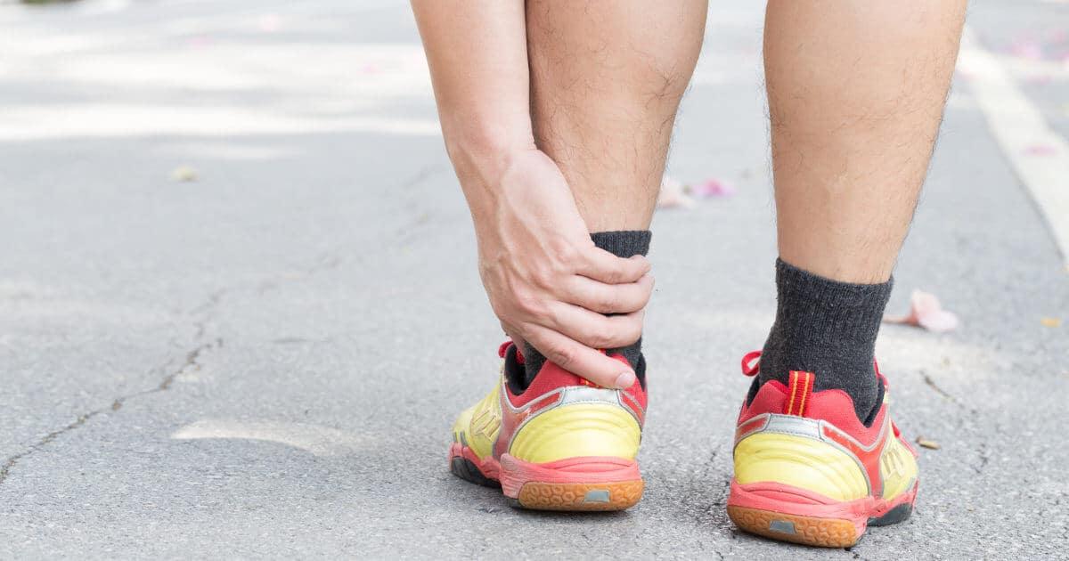 Jogger hält sich seine schmerzende Achillessehne