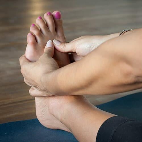 Eine Frau massiert ihren nackten Fuß am Fußballen.