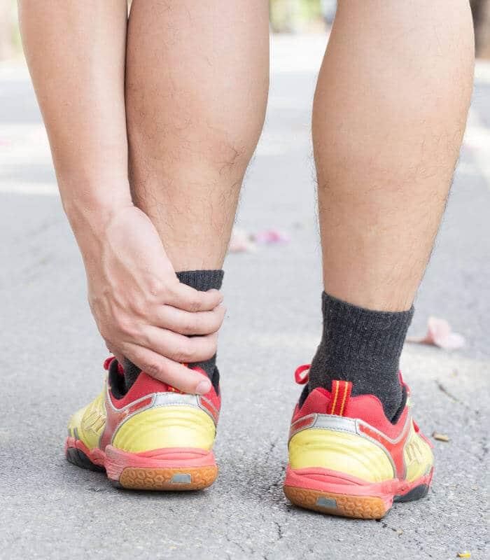 Mann hält sich Achillessehne bei Fußschmerzen