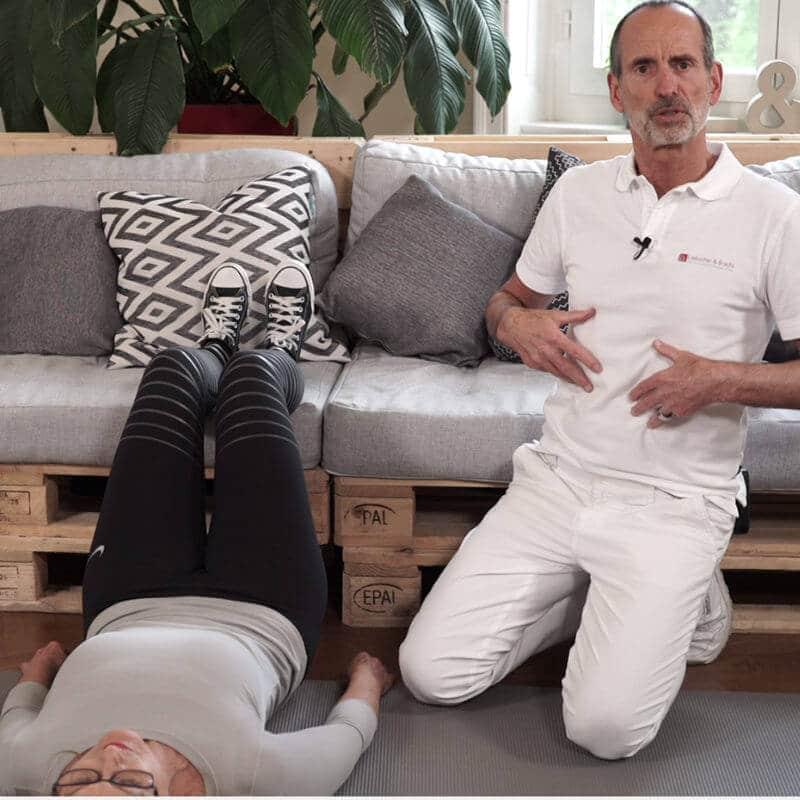Eine Frau in der Stufenlagerung. Roland Liebscher-Bracht kniet neben ihr und deutet auf seinen Bauch, dabei erklärt er etwas.