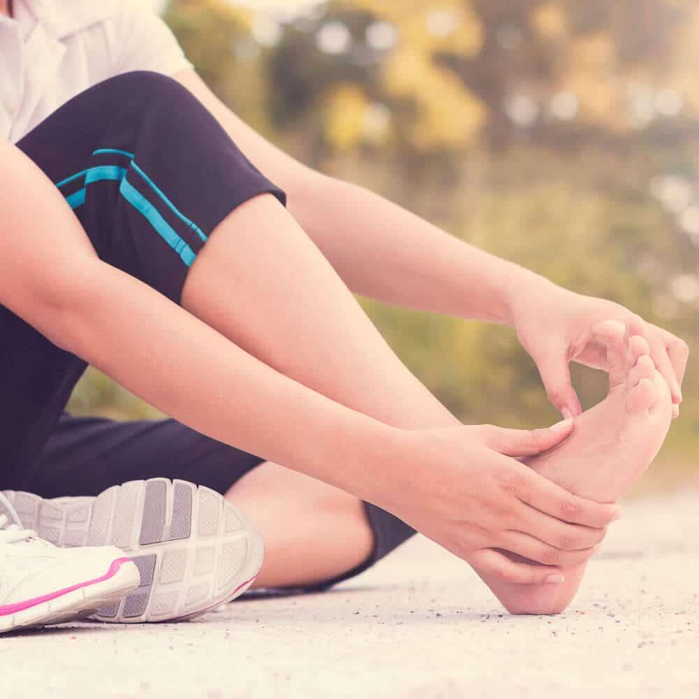 Frau hält sich nach dem Joggen den schmerzenden Fuß