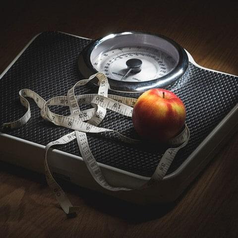 Ein Maßband und ein Apfel liegen auf einer Waage.