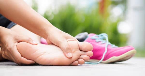 Eine Frau umfasst mit beiden Händen ihren Fuß, zu sehen ist die Fußsohle.