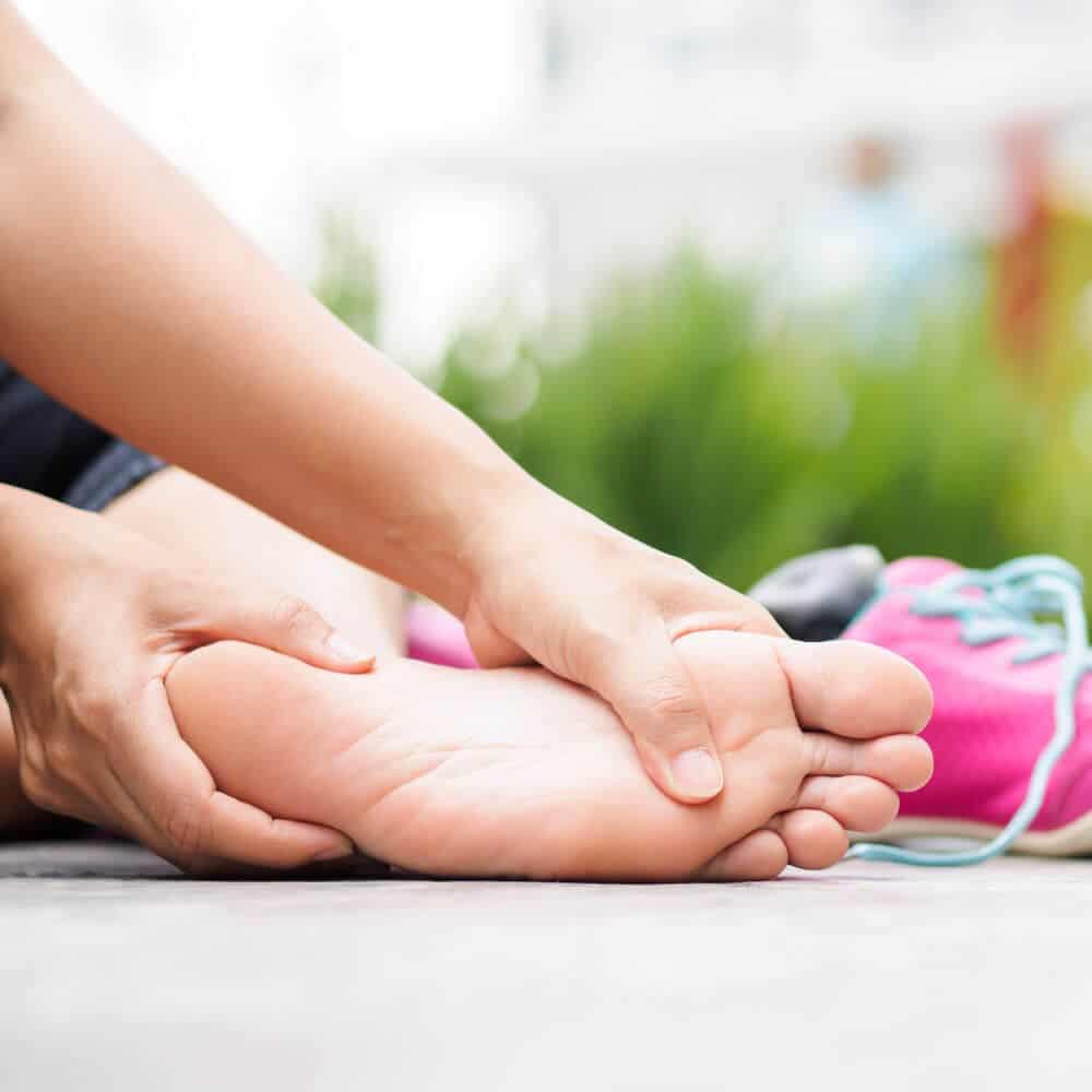 Frau hält sich den Fuß bei einer Plantarfasziitis