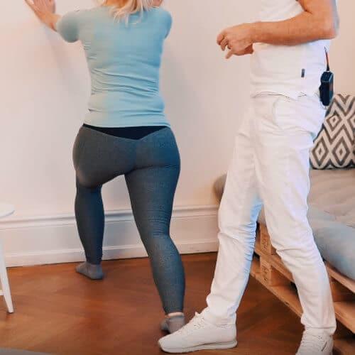 Eine Frau steht an einer Wand, stützt sich mit den Armen ab. Ein Bein steht leicht gebeugt an der Wand, das andere weit weggestreckt nach hinten. Roland Liebscher-Bracht steht hinter ihr.