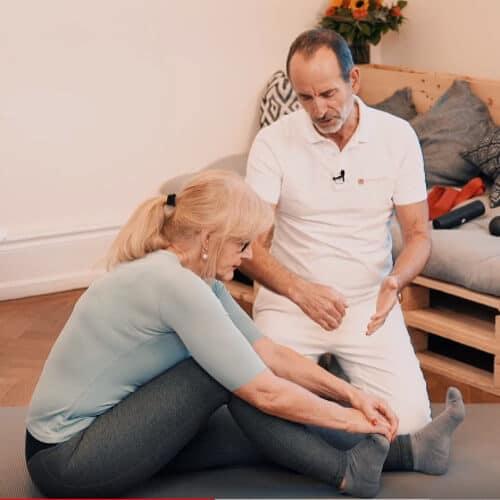 Roland Liebscher-Bracht zeigt einer Frau eine Übung zur Dehnung der Fußsohle bei Fersenschmerzen, Hammerzehe und Plantarfasziitis. Dazu wird die Ferse aufgestellt und die Zehen mit der Hand in Richtung Körper gezogen.