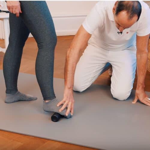 Roland Liebscher-Bracht zeigt einer Frau eine Faszien-Rollmassage am Fuß mit der Mini-Faszienrolle. Sie rollt mit der Fußsohle darüber. Die Übung lindert Beschwerden einer Plantarfasziitis.
