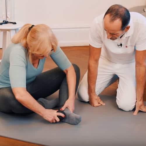 Faszien-Rollmassage mit der Mini-Kugel bei Hammerzehen und Fersenschmerzen und Plantarfasziitis. Frau rollt sprialförmig mit der Mini-Kugel über die verspannten Stellen an der Fußsohle.