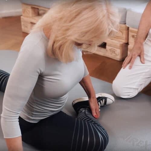 Eine Frau auf einder Bodenmatte hat ein Bein weit nach hinten gestreckt liegend, das andere zieht sie angewinkelt zu sich heran. Der Rücken ist aufrecht. Neben ihr kniet Roland Liebscher-Bracht.
