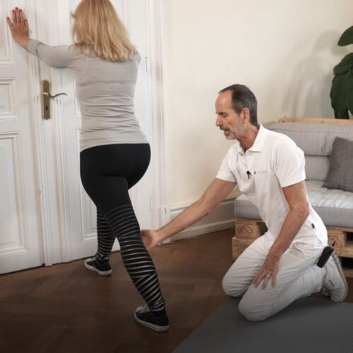 Eine Frau stuetzt sich mit ausgestreckten Armen und den Haenden an der Wand ab. Ein Bein ist nach vorne angewinkelt und das zweite nach hinten komplett ausgestreckt. Roland Liebscher-Bracaht kniet neben ihr und korrigiert ihre Bein-Position.