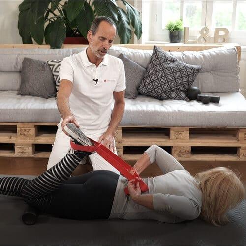 Roland Liebscher-Bracht zeigt einer Frau eine Übung. Sie liegt bäuchlings auf einer Matte. Ein Bein zieht sie mithilfe der Übungssschlaufe in Richtung Gesäß, unter dem Knie liegt eine Faszienrolle.