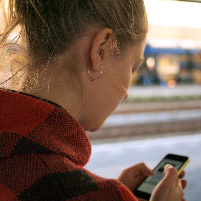 Eine Frau schaut auf ihre Smartphone, ihr Kopf ist dabei nach unten geneigt.