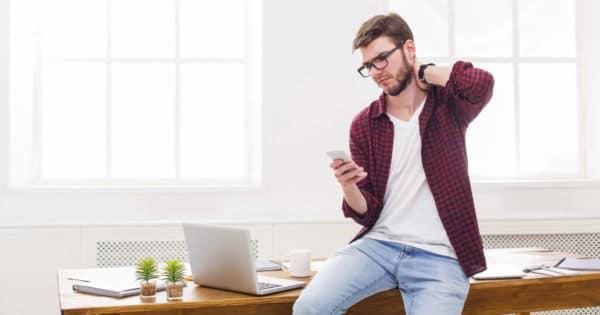 Ein Mann sitzt auf seinem Büro-Schreibtisch, schaut auf sein Smartphone und hat Nackenschmerzen