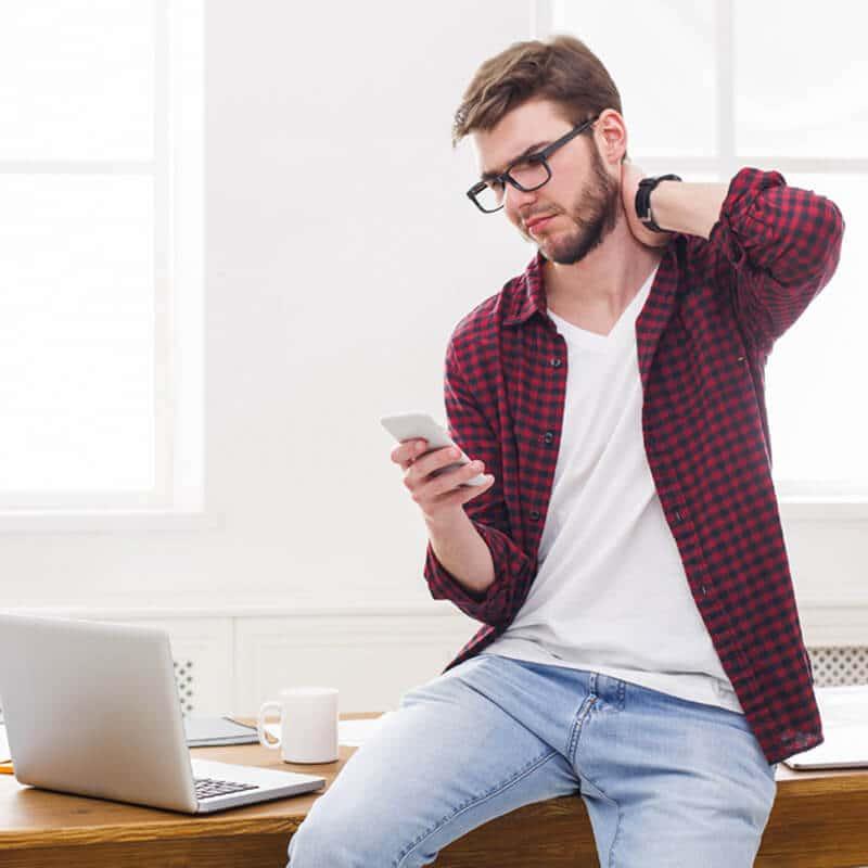 Mann mit Smartphone und Nackenschmerzen