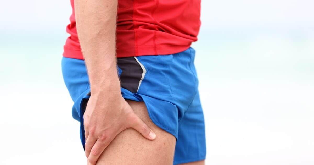 Ein Jogger hält sich die schmerzende Außenseite seines überspannten Oberschenkels