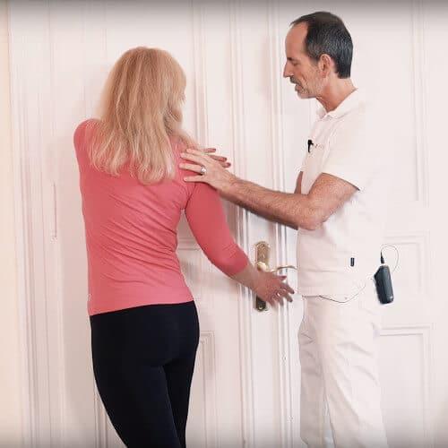 Eine Frau steht halb-seitlich an einer Wand und bekommt von Roland Liebscher-Bracht eine Übung gezeigt