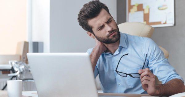 Ein Mann am Laptop hat Nackenschmerzen im Büro