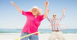 Senioren spielen Hula Hoop am Strand