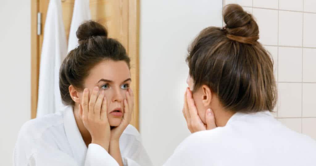 Eine Frau betrachtet ihre schmerzenden Augen vor dem Spiegel, indem sie sich die Augen mit beiden Händen aufhält