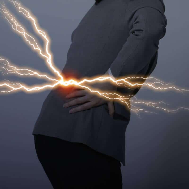 Eine Frau hat einen Bandscheibenvorfall und hält sich vor Schmerzen ihre Lendenwirbelsäule, aus der Blitze schießen