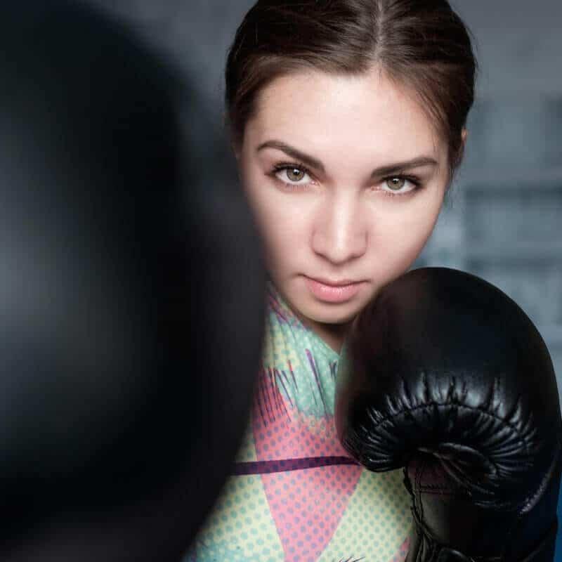 Ein junge Frau mit Boxhandschuhen blickt wild entschlossen in die Kamera und möchte die Ursache ihres Bandscheibenvorfalls bekämpfen