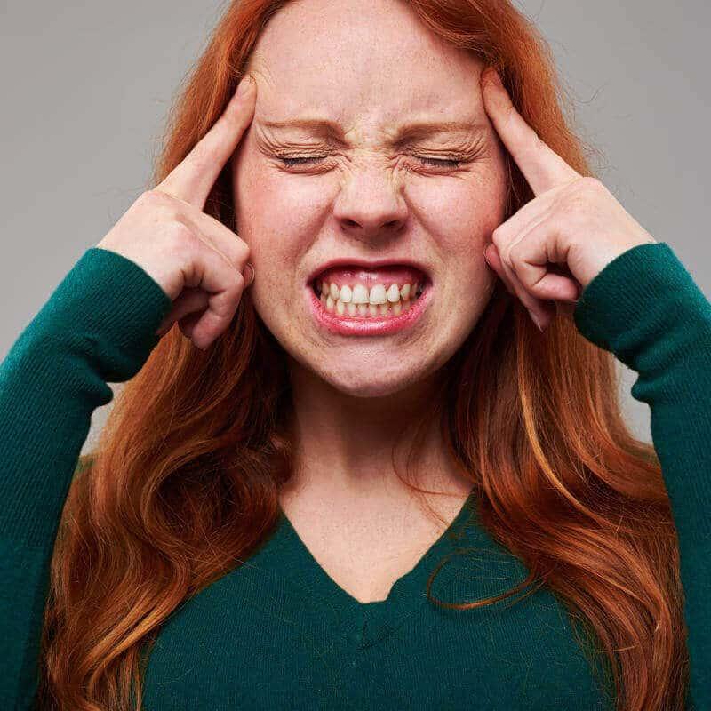 Frau beißt ihre Zähne fest zusammen und macht ein verbissenes Gesicht
