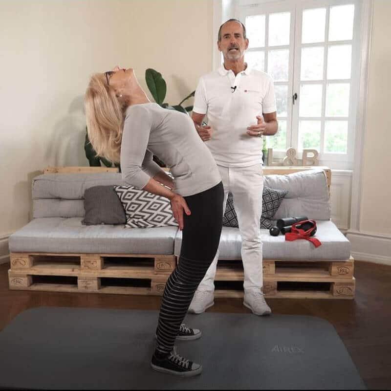 Eine Frau macht eine Dehnungsübung gegen Gesäßschmerzen, indem sie sich im Stehen überstreckt