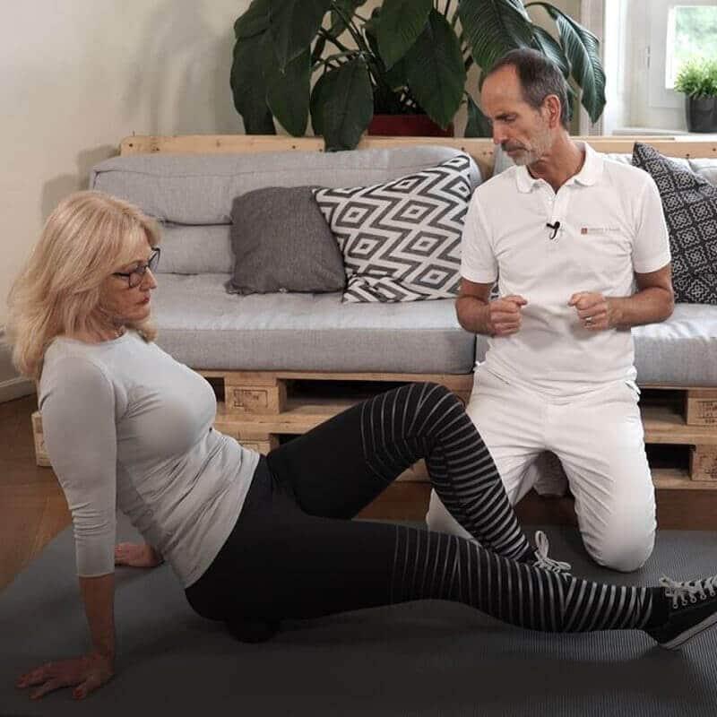 Eine Frau macht eine Faszien-Rollmassage gegen Gesäßschmerzen, indem sie mit der Medi-Faszienkugel ihre linke Gesäßhälfte bearbeitet