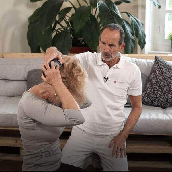 Roland Liebscher-Bracht zeigt Patientin wo sie die Faszienrolle am Hinterkopf ansetzen muss