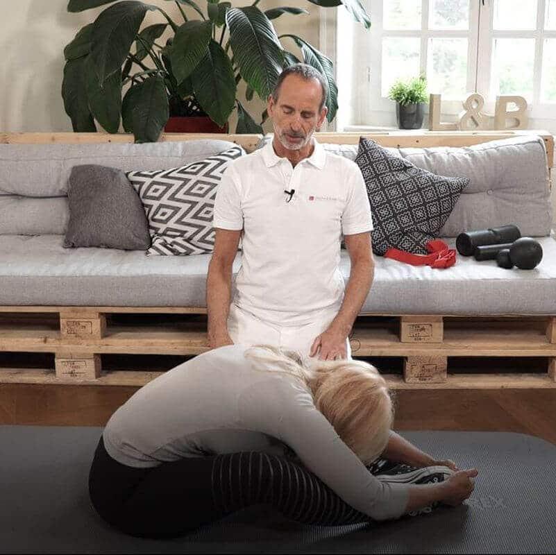 Eine Frau dehnt ihre Lendenwirbelsäule, indem sie im Sitzen ihre Fußsohlen zusammenführt und die Knie nach außen fallen lässt