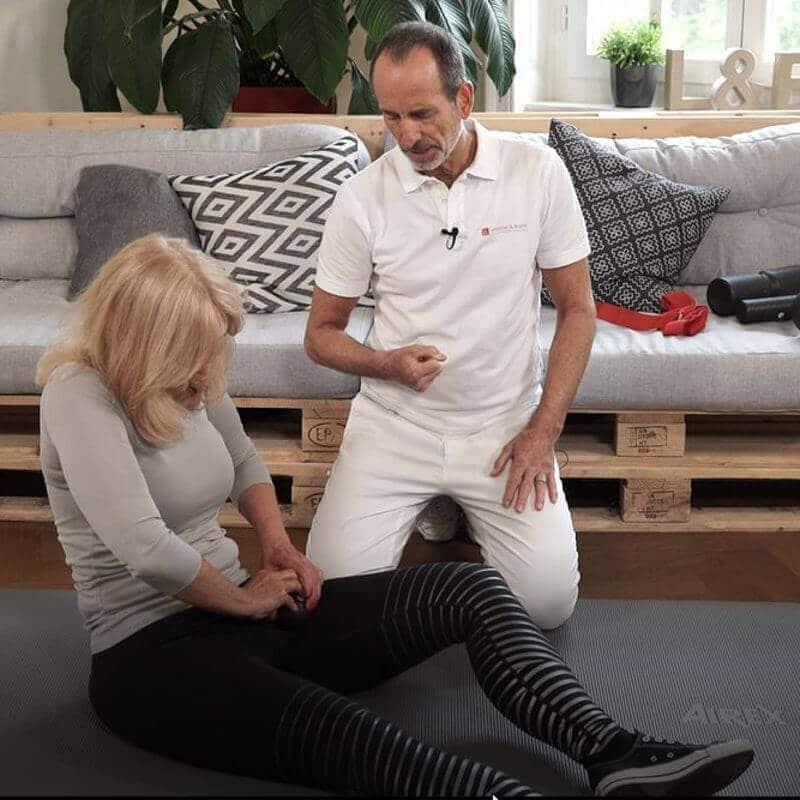 Eine Frau rollt mit der Mini-Faszienkugel an der Innenseite ihres linken Oberschenkels